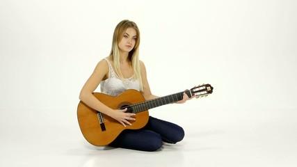 Young beautiful caucasian woman in casual playing guitar.