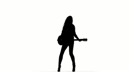 Silhouette of a young girl playing dancing on electric guitar on