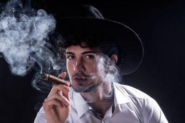 Handsome man holding cigar with smoke