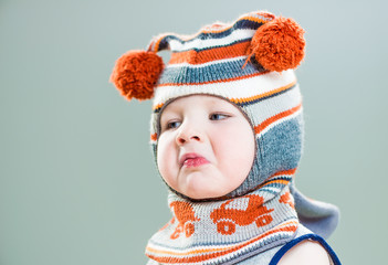 little boy portrait in hat with disgust emotion