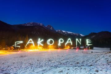 Zakopane sign under Tatra mountains at night, Poland