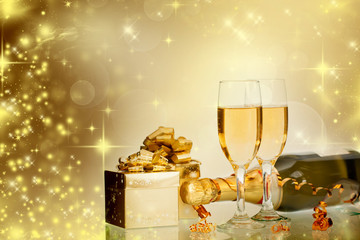 Glasses with champagne and bottle over sparkling background