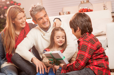 Children opening Christmas presents at home with their parents