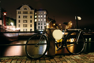 Bicycle at night near the pier on the background