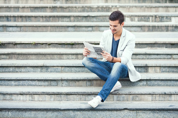 Young man sitting on the stairs reading newspaper