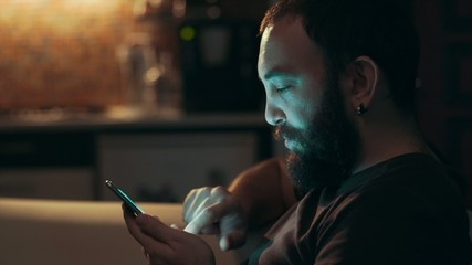 Young man using his smart phone in the dark