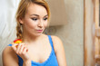 Candid portrait pensive woman teenage girl eating apple fruit