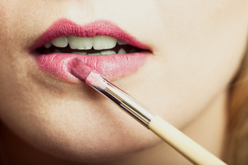 Part of face. Woman applying pink lipstick with brush