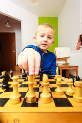 Little boy clever child playing chess thinking,
