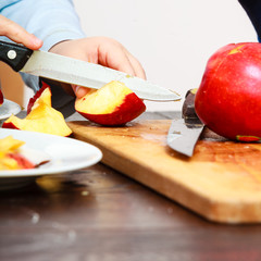 child cut apple with a kitchen knife
