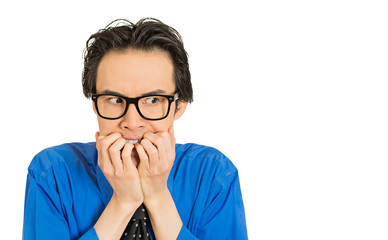 nerdy young guy with glasses biting his nails looking anxious