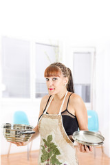Woman in apron shrugging in the kitchen holding saucepan