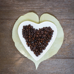 coffee grains and leaves over wooden background