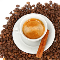 The white cup of espresso with grains and cinnamon stick