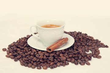 The cup of black coffee with grains and cinnamon stick, toned