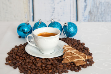 white mug of hot coffee with four blue christmas ball