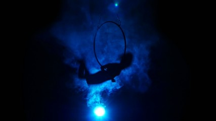 Aerial acrobat woman on circus stage. Silhouette on a blue