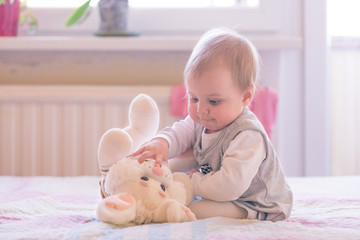 10 months old baby girl playing with plush rabbit