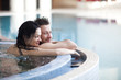 Couple relaxing in jacuzzi of spa center  - 74467015