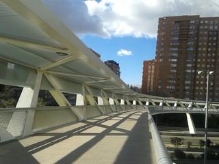 White steel footbridge over a highway
