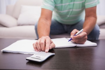 Man working out his finances on the couch