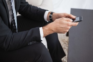 Businessman sending a text on his couch