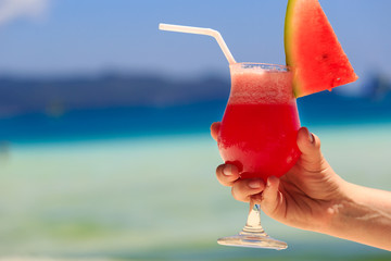 hand holding watermelon cocktail on beach