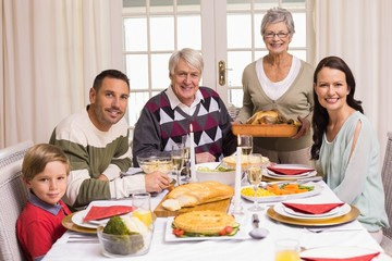 Grandmother holding turkey roast with family