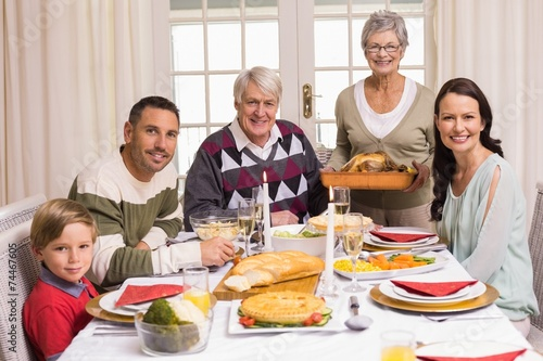 canvas print picture Grandmother holding turkey roast with family