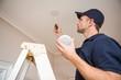 Handyman installing smoke detector - 74468237