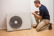 Focused handyman fixing air conditioning - 74468255