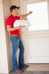 Delivery man holding pizza while knocking on the door