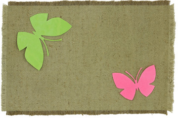 cardboard butterfly on green coarse cloth