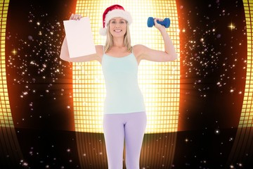Composite image of festive fit blonde holding page and dumbbell