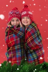 Composite image of festive little girls under a blanket