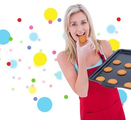 Composite image of happy blonde eating hot cookies