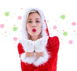 Composite image of festive blonde blowing a kiss