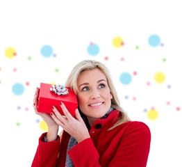 Composite image of festive blonde holding red gift
