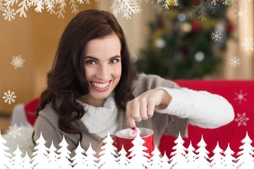 Brunette dunking marshmallow in hot chocolate e at christmas