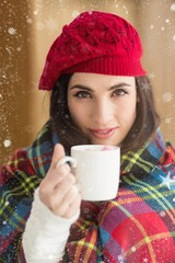 Composite image of brunette with cover holding mug