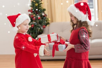 Composite image of festive little siblings holding gifts