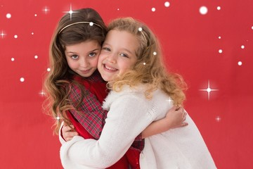 Composite image of festive little girls hugging and smiling