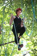 woman climbing in adventure rope park in safety equipment