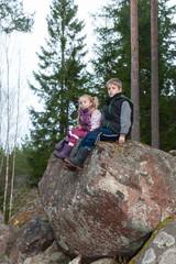 Kinder sitzen auf einem großen Felsen und ruhen sich aus
