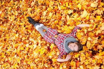 Junge attraktive Frau im Herbstlaub liegend