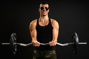 Young man in sunglasses exercises with dumbbells