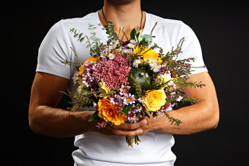 Man in white shirt holding bouquet of flowers on dark background