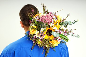 Man with his back holding a flowers with autumn decorations