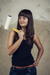 girl holding paint roller over grunge background