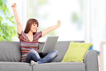 Happy woman working on laptop and gesturing happiness